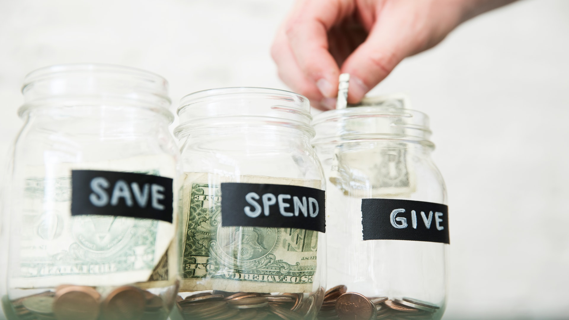 3 Jars labeled Save, Spend, and Give with money in them. Learn how to fill all three at Brookwood Church