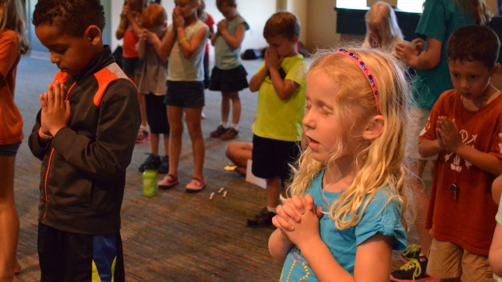 A group of kids praying at Brookwood Church