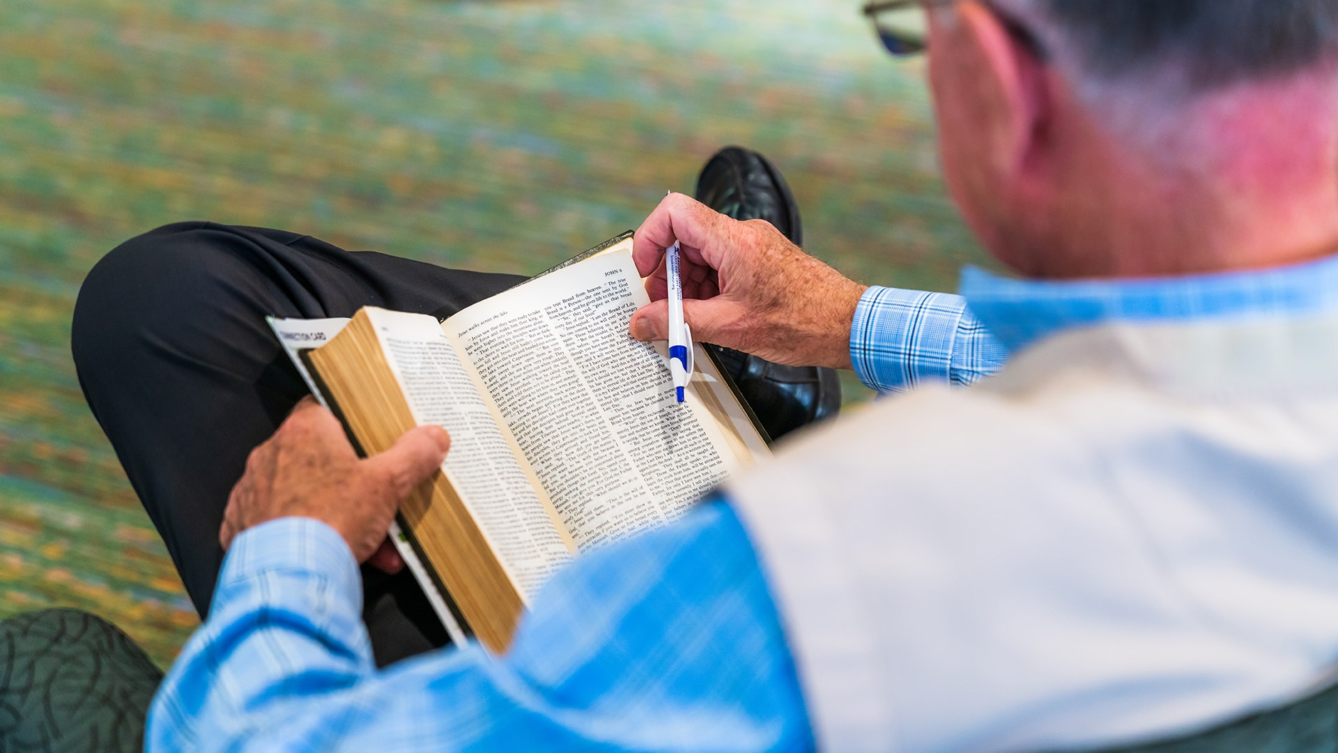 A man, pen in hand, reading his Bible at Brookwood Church