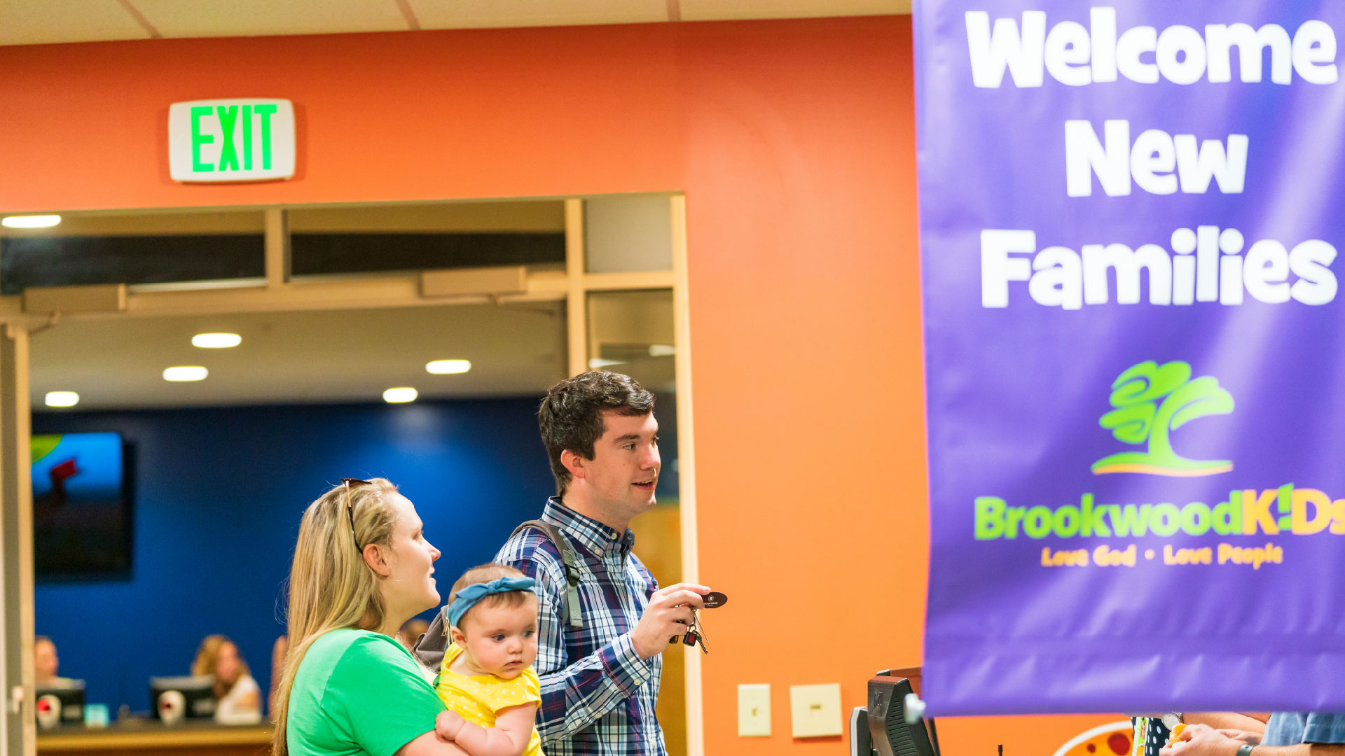 A family with a baby stands in front of the Welcome New Families banner at Brookwood Church