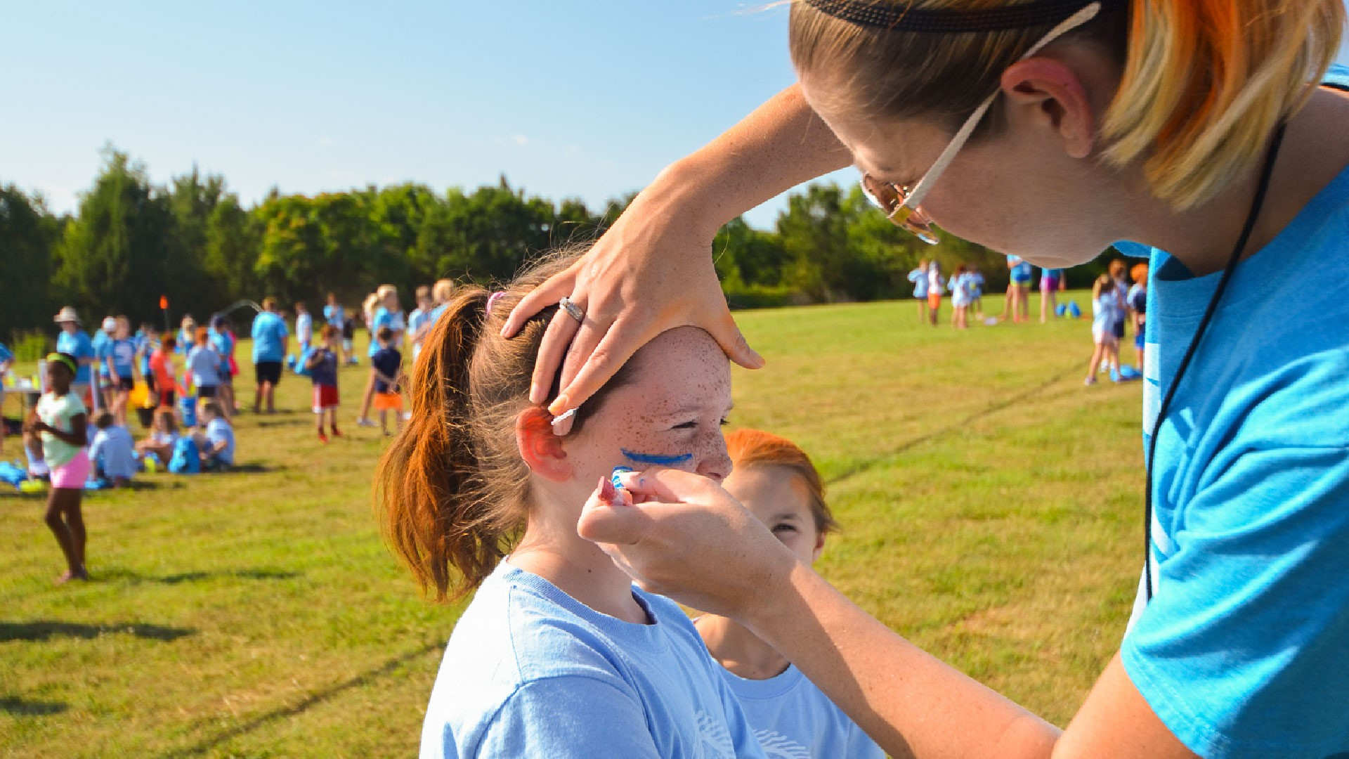 A recreation volunteer paints team colors on the faces of children at Brookwood Church