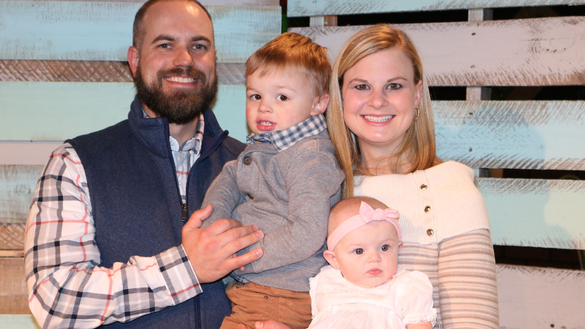 A family with two small children smiling for Brookwood Church parent dedication